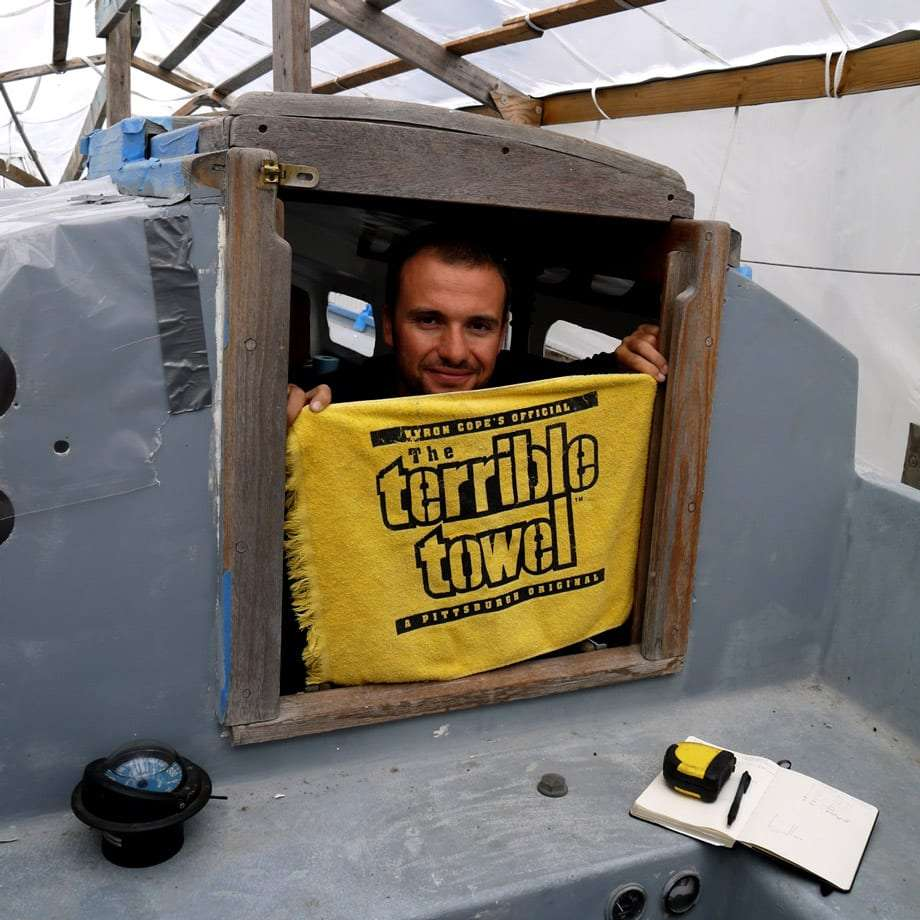 a man peeking through a window holding a yellow towel which reads The Terrible Towel, Pittsburgh Steelers