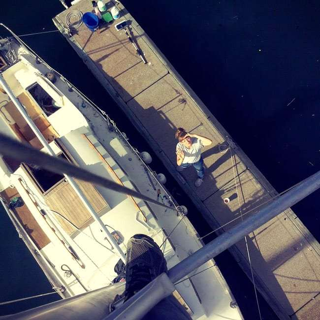 looking down from the top of a sailing boat mast at a crew member on dock, looking back up