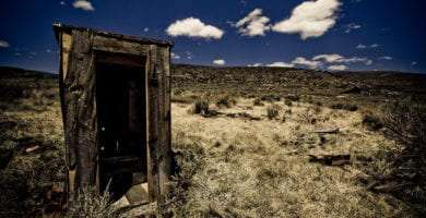 an outhouse in a barren field
