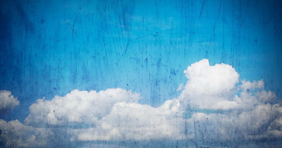 grunge treatment to a photo of clouds in the big blue sky