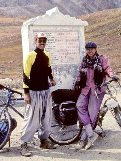 a man and woman stand in front of a sign written in a foreign language, bicycles at their sides