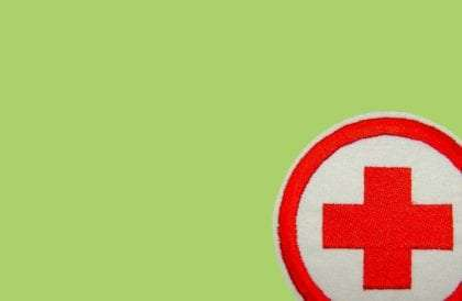 a red cross patch on a green background