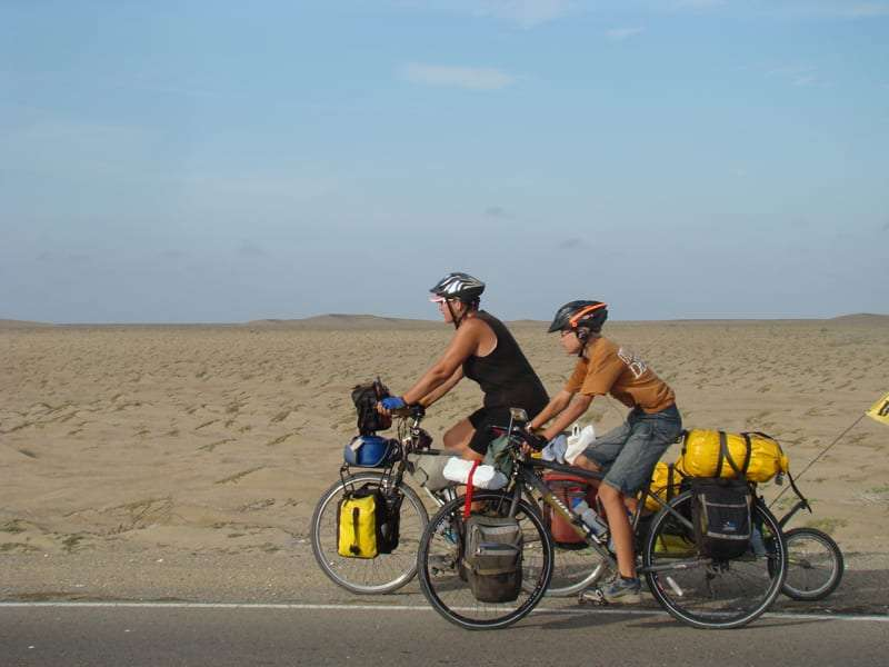 a mother and son ride bicycles through the desert