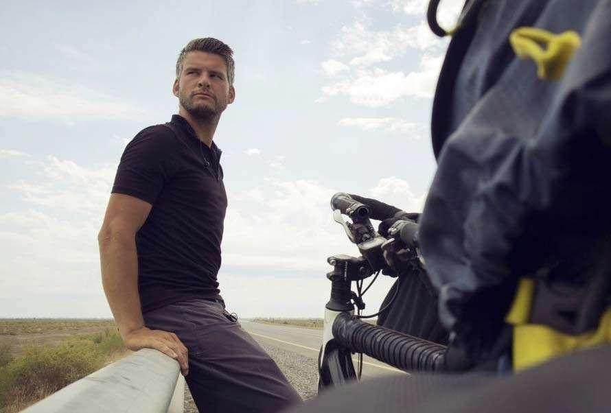 a man leans against a guard rail, near a bicycle