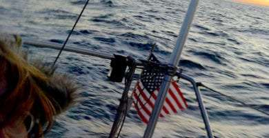 an american flag, a woman on watch on a sailboat, and the open sea