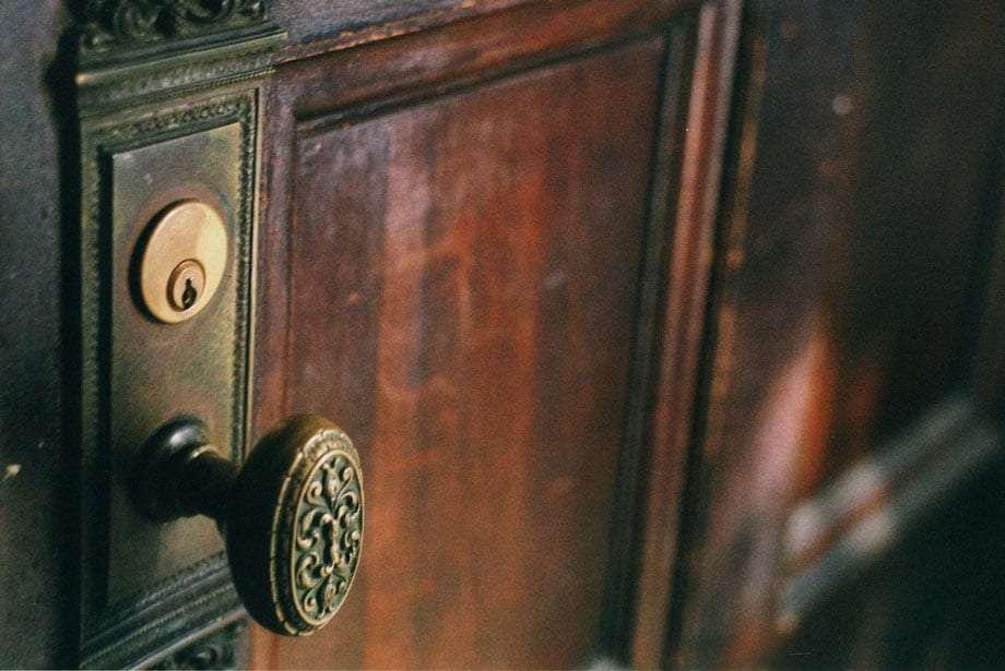 an old brass doorknob on an old wooden door