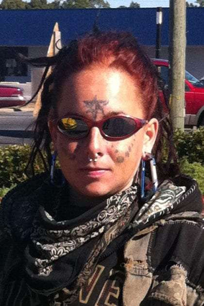 a young train hopping girl, red hair, sunglasses and tattoos on her face