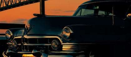 a 1950's Cadillac silhouetted against a burning orange sky, the Astoria-Megler Bridge in the background
