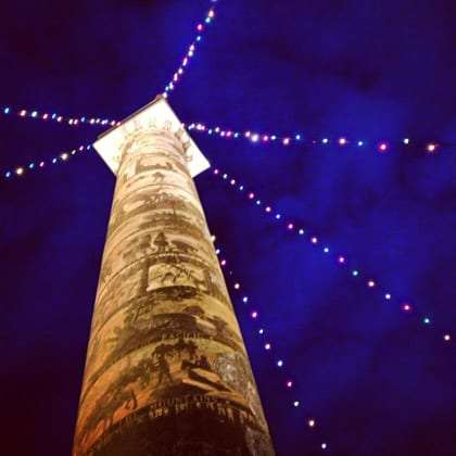 nighttime, a tower projecting into the sky is covered in sand paintings and strung with lights