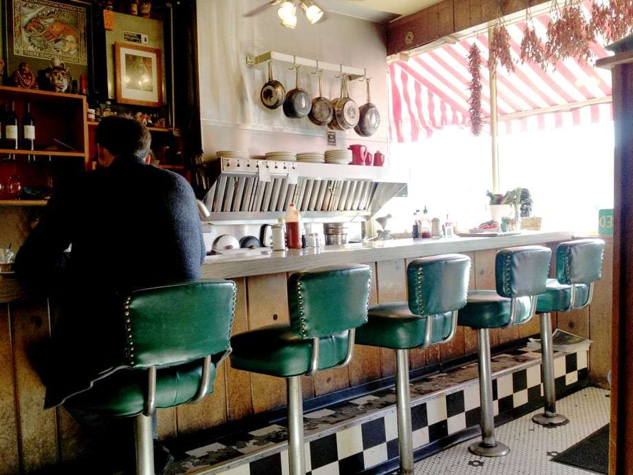 a man sits at one of several vintage barseats that line the counter of a cafe