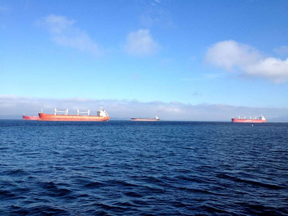 large freight ships with shipping containers rest in the columbia river near astoria oregon