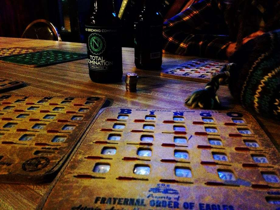 rustic bingo cards and ninkasi beers on a table in a bar