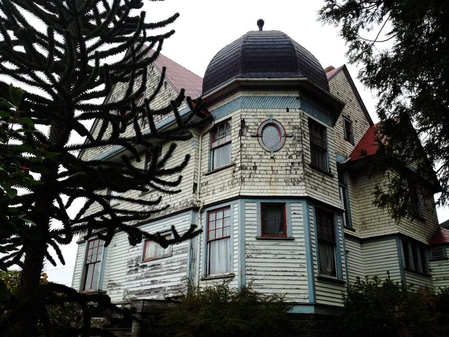 a beautiful victorian mansion stands in a bit of disrepair