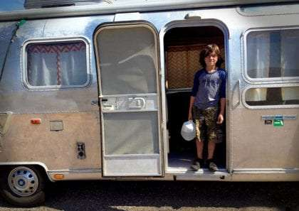 an adolescent boy holds a water jug while standing in the door of a vintage airstream travel trailer