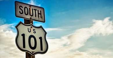 a Highway South 101 sign stands stalwart and brilliant against a Pacific Ocean sky