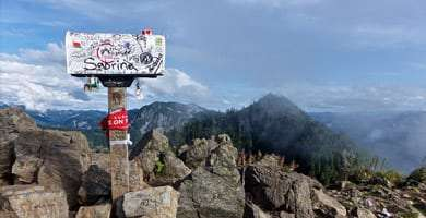 a mailbox, tagged with a plethora of names, stands atop some distant mountain peak
