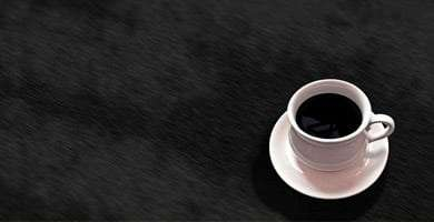 a cup of coffee, black, sits against a dark background