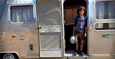 a young man holding a gallon of water stands in the doorway of a silver vintage travel trailer
