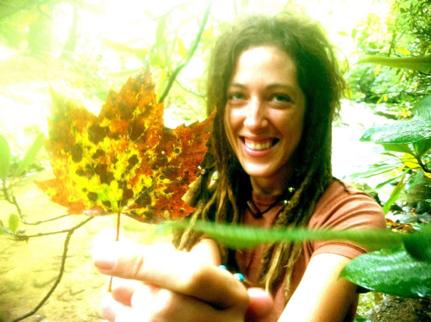 a woman smiling, holding a multi-colored leaf