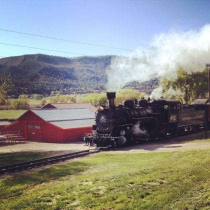 A steam train rolls through a campground in colorado
