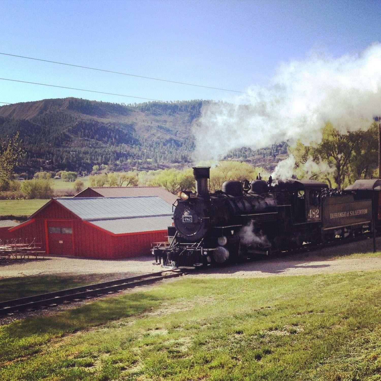 A steam train rolls through a campground in colorado