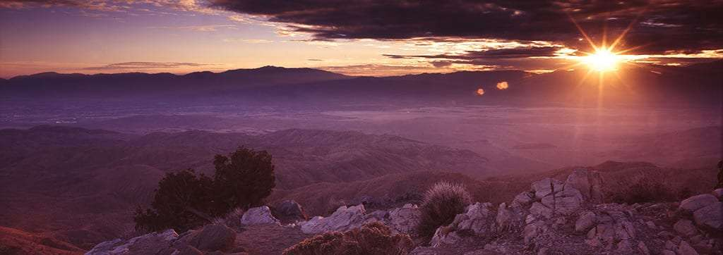 purple lighting falls over a wide valley as the sun leaves the clouds and prepares to set