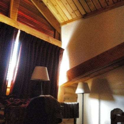 the inside of a log cabin bedrom, light pouring in faintly from a window but dramatic enough to cast chiaroscuro the room