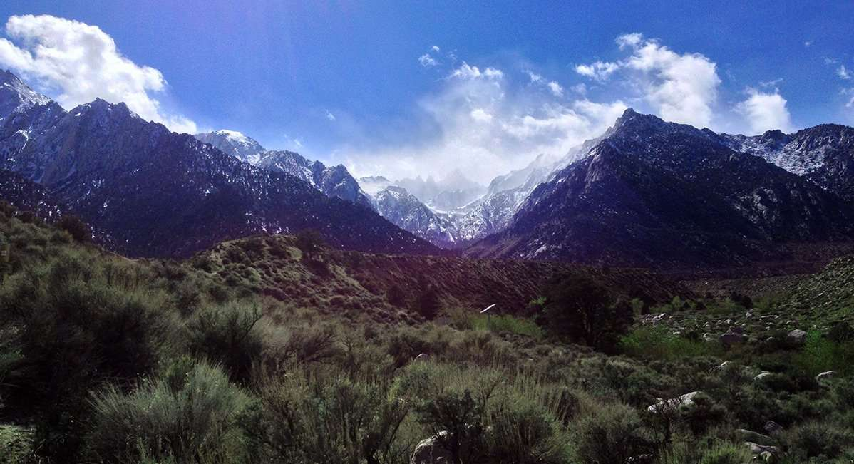 beyond dull green fields of sage brush, over the foothills of the sierra nevadas, rises mount whitney, covered in snow