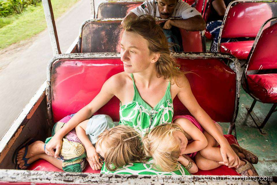 the wind blows freely through a bus window, through the hair of a young mother holding her sleeping daughters