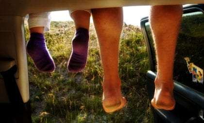 a father and daughters feet dangling from the roof of a minivan, as seen by a mother first thing in the morning from inside looking through the back