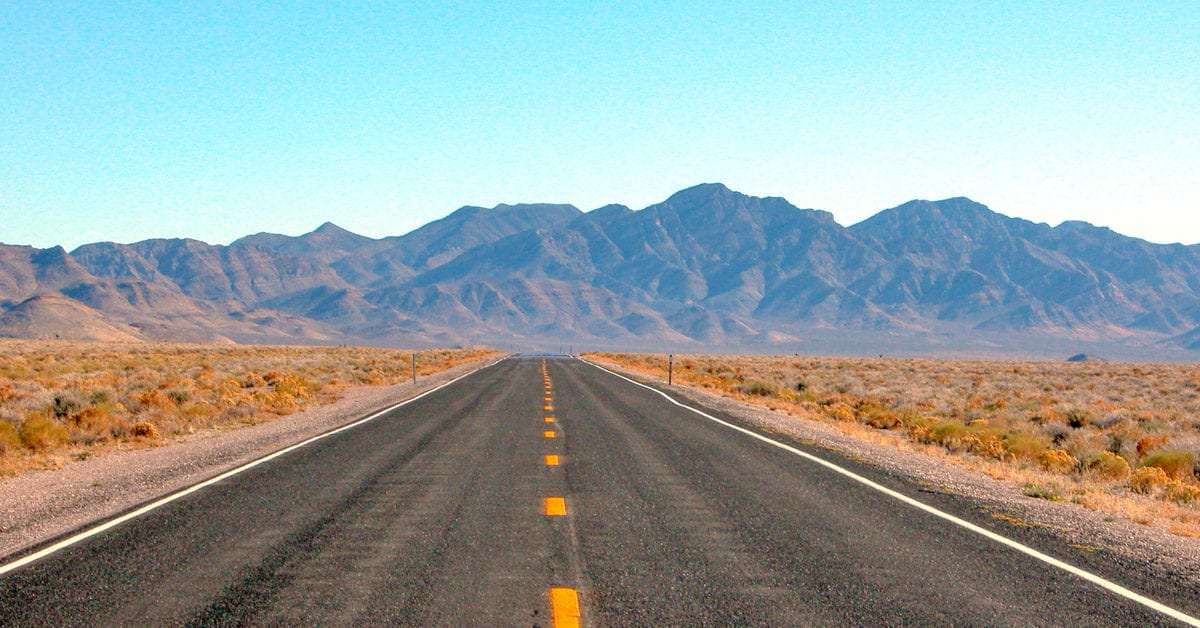 Highway 375 south of Rachel wears a single dotted yellow line endlessly straight into the desert, toward mountains climbing into a blue sky