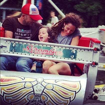 A family tearing through the good times on an amusement park ride