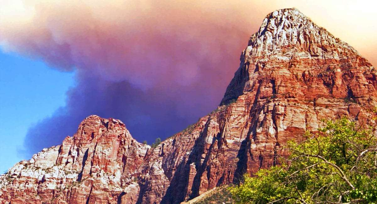 purple and red smoke plumes above the red and silver canyon walls of Zion National Park