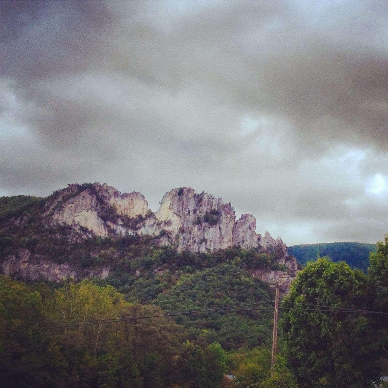 Craggy mountain cliffs jut from a wooded hillside