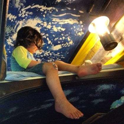 A three year old dangles from the top bunk of a vw bus