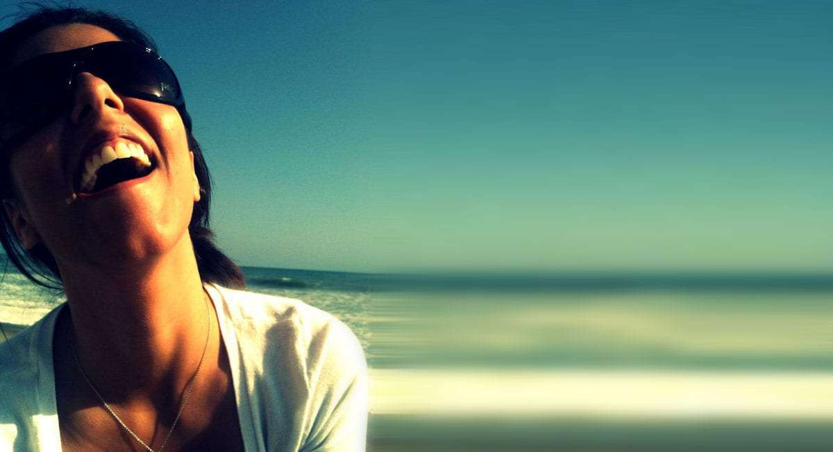 a young woman, beautiful and on the beach, laughs teeth wide blaring, sunglasses doing little to hide the happiness in her eyes