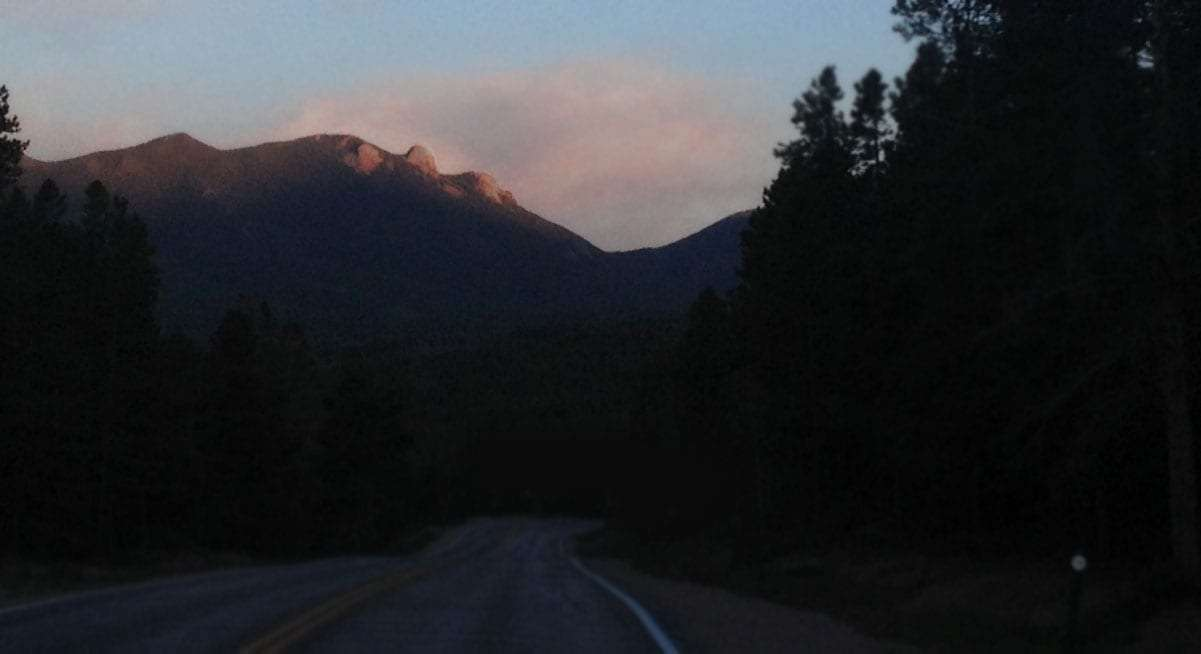 as though contours of a mountain, the profile of the sleeping giant stands prominent form a particular dark road through the national forest just before sunset near Nederland, Colorado