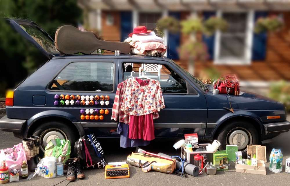a small hatchback car adorned in enough clothes to serve the purposes of a young woman beginning a journey into the wide world...