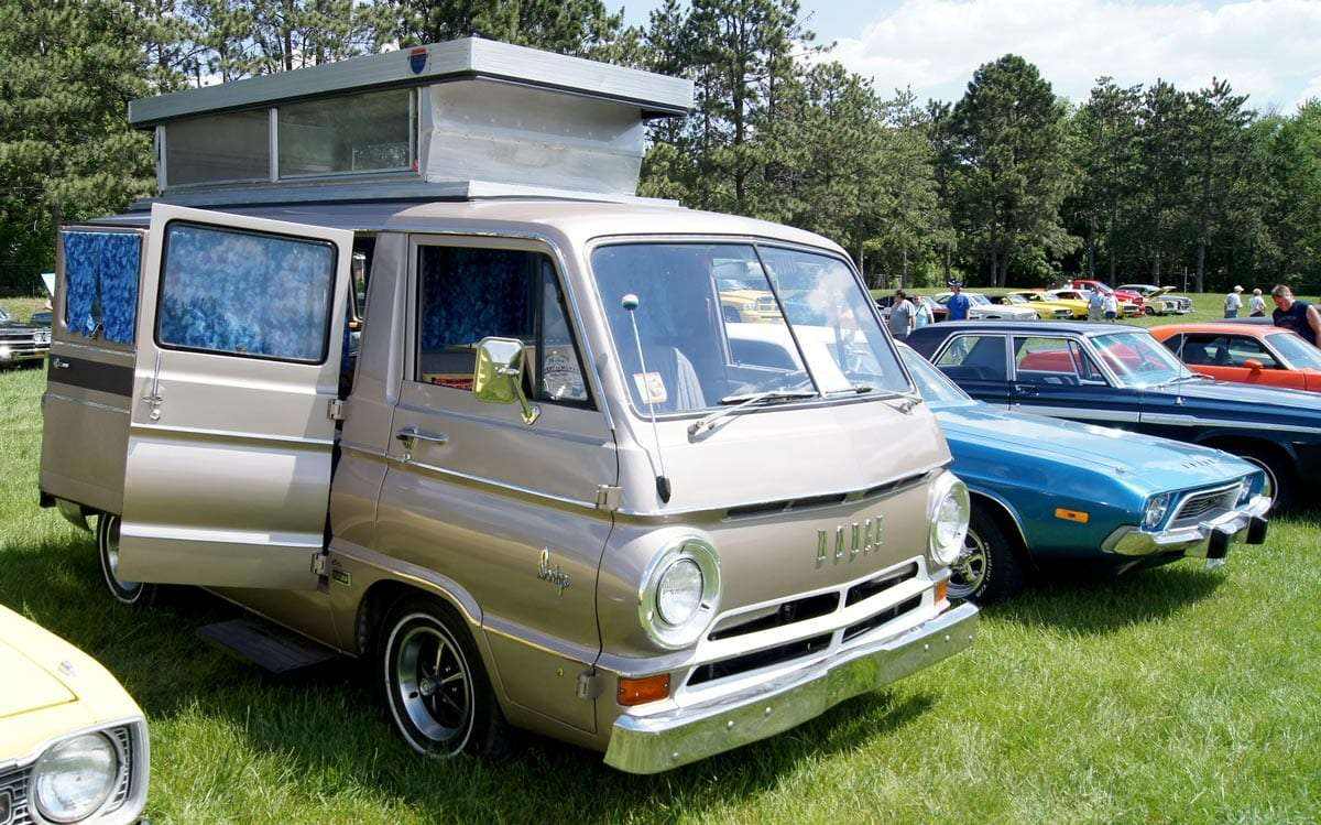 a champagne colored van from the 1960s with a pop top and other camping features