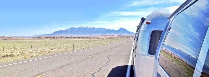 the henry mountains disappear over the horizon as a van towing an airstream rolls down a two lane highway