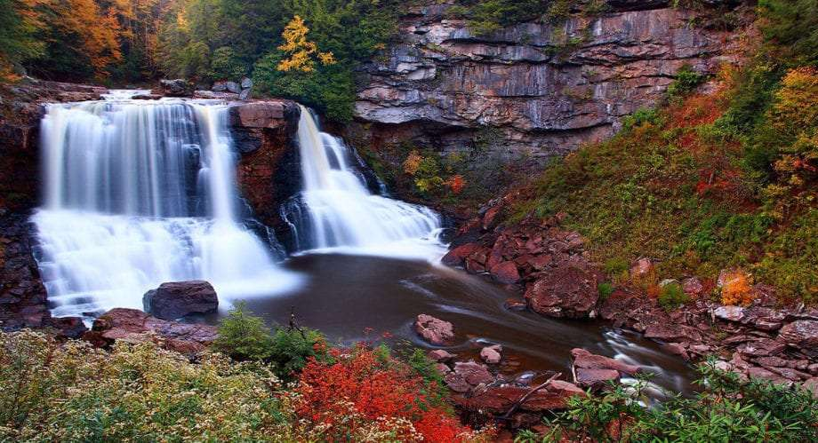 white water falls over a large cliff as autumn changes the trees all around