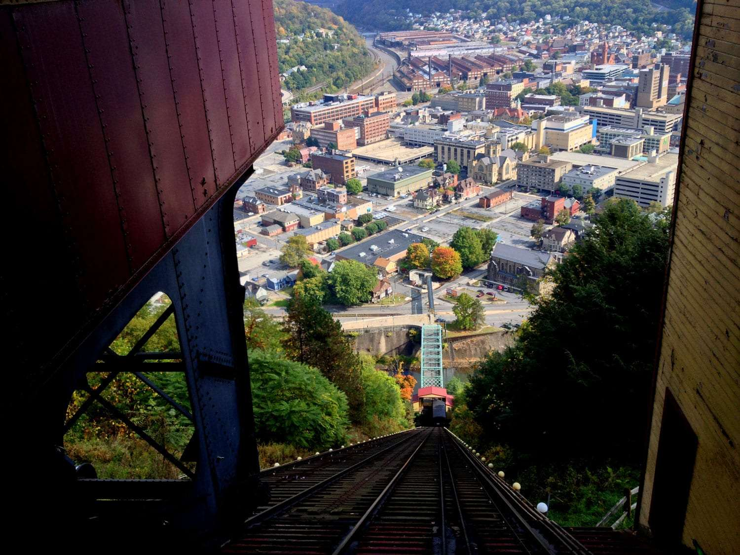a stack of buildings toppling over like it hadn't been dusted since 1972 fills a tree-lined valley, a turquoise bridge glows as a funicular elevates