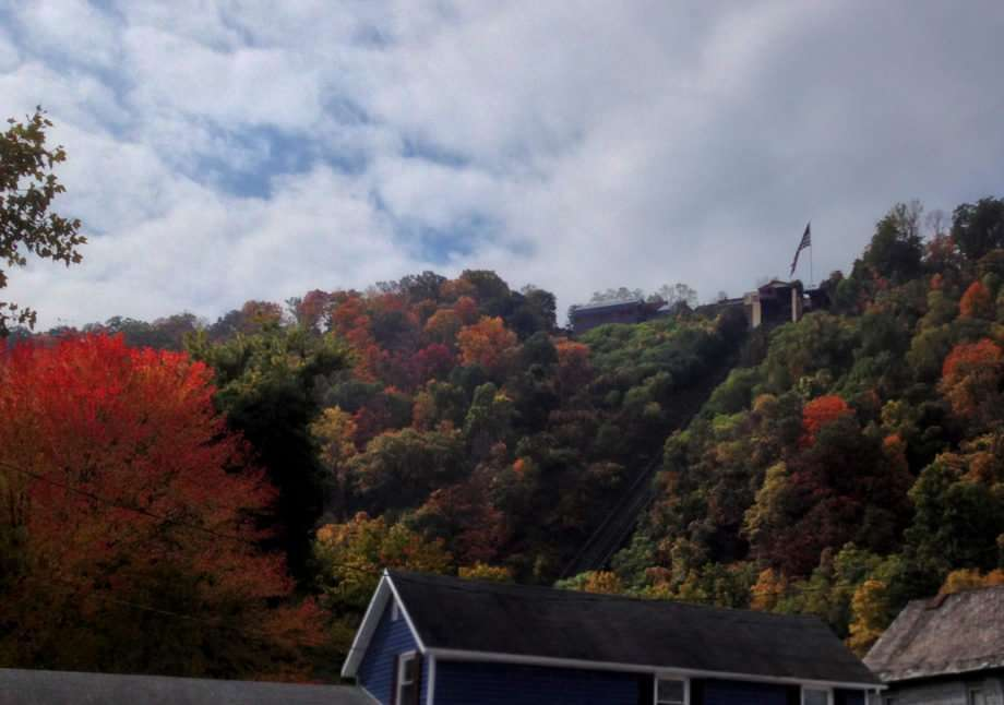 a flag flies above a seemingly small structure, tracks extending from it steeply down a hill. Vivid reds and yellow-oranges speckle an otherwise green valley wall.