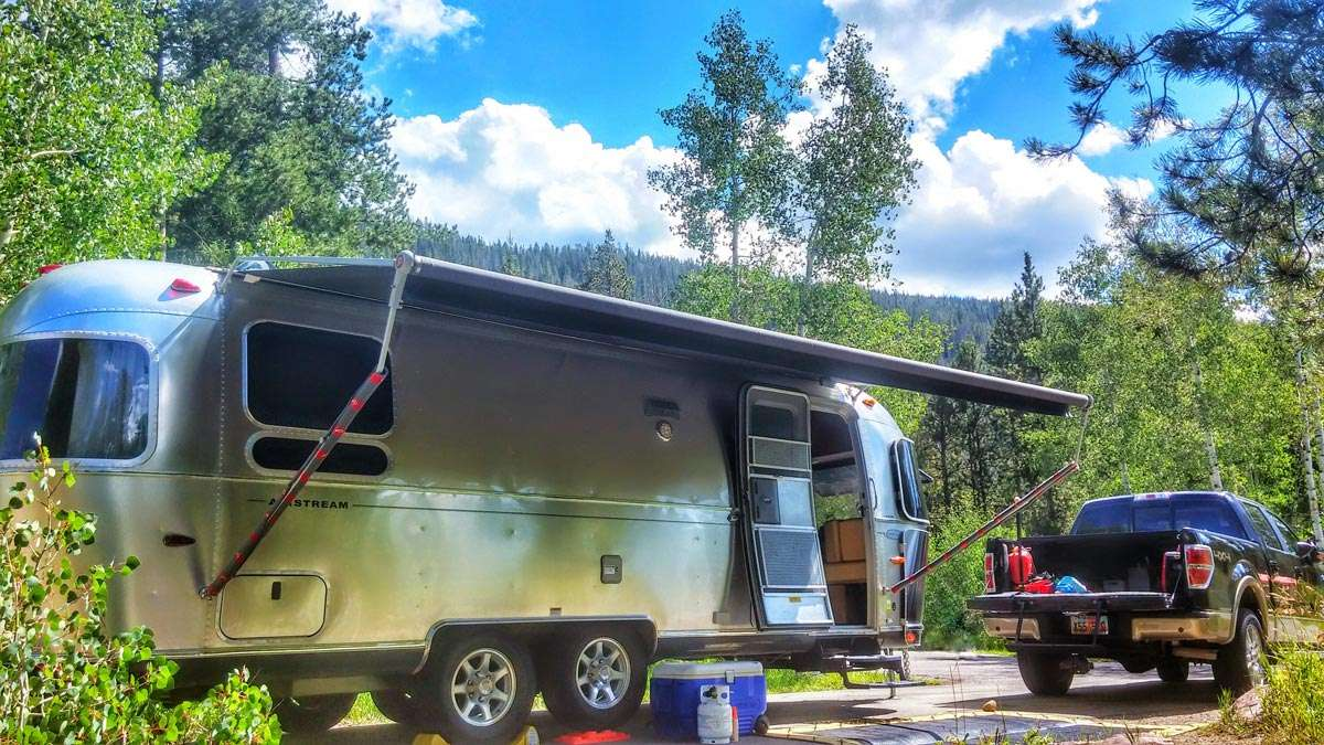 a beautiful silver travel trailer reflects the forest around