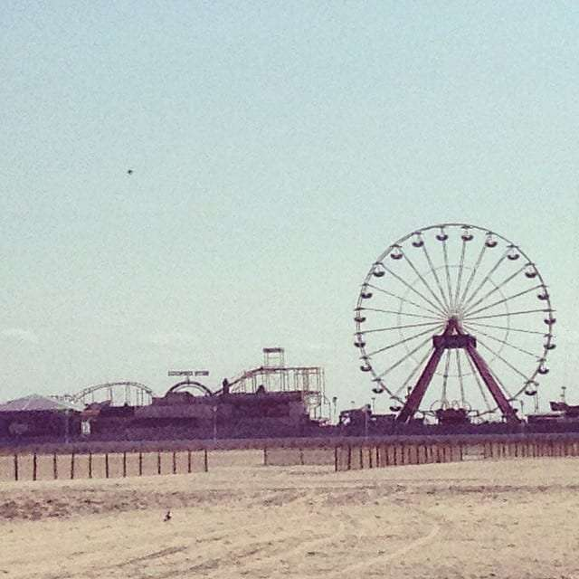 a ferris wheel and a rollercoaster at the southern end of a long stretch of beach