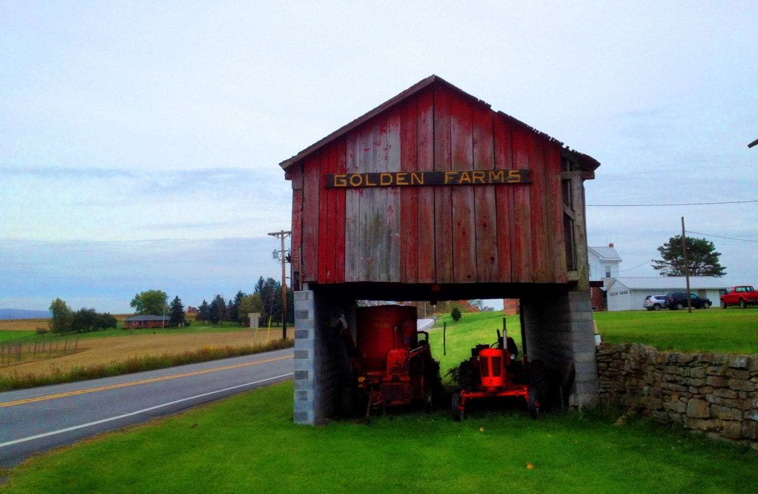 old farming equipment rests beneath a barn in the PA countryside