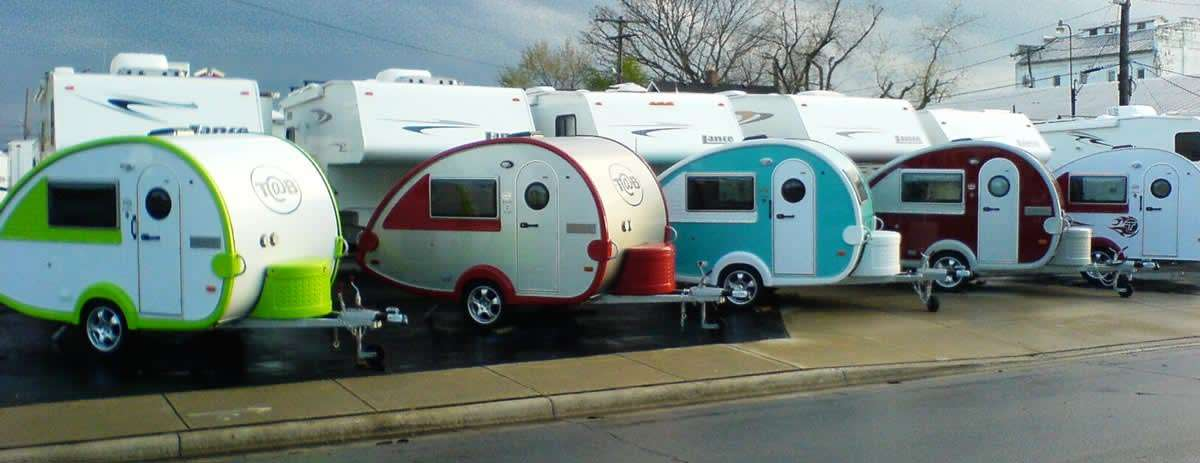 several small, teardrop-shaped trailers in a lot of RVs