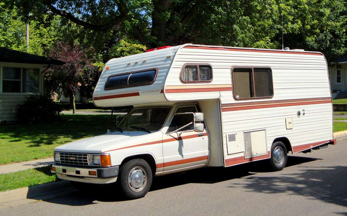 older brown and orange striped camper on a toyota truck chassis
