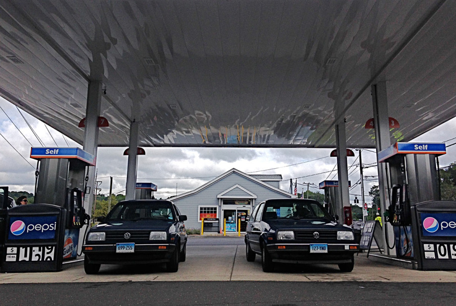 two late 80's model VW Golfs, hatchback style cars, at a gas station