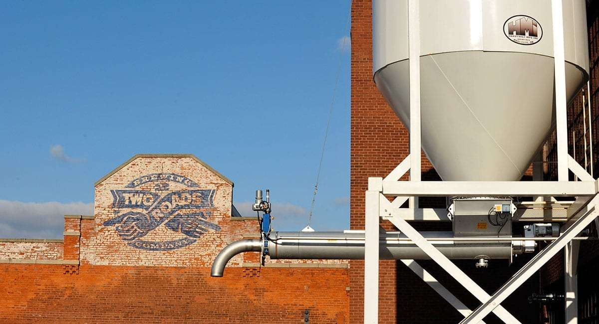 a sign boasting a distressed version of the company logo painted on a brick wall, a new brewing tank in the foreground